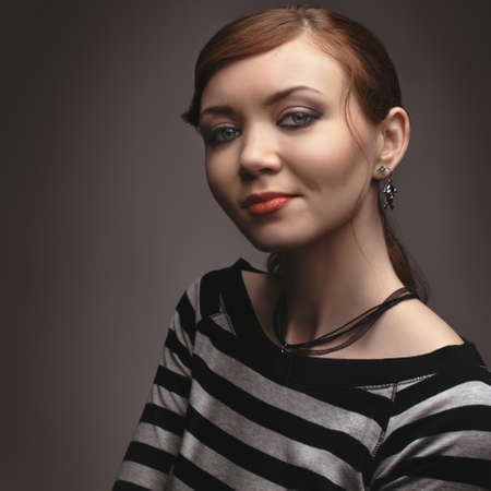 beautiful sexy slim girl posing sitting on a black cube, in gray studio