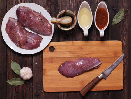 raw duck breast on a wooden table. Grill pan. tasty recipe. composition of objects view from the top Stok Fotoğraf