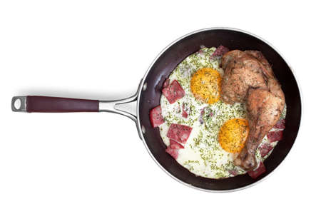 fried eggs with sausage and chicken leg on a frying pan. is isolated on white background