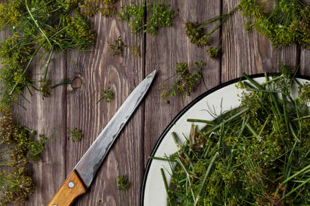 dill on a wooden table. knife and plate