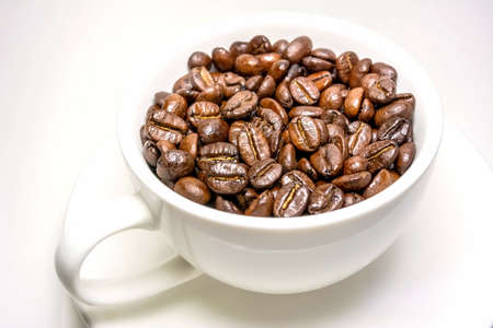 medium roasted coffee beans in a white cup photo