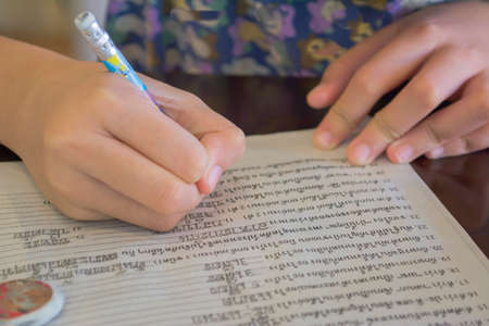 kids writing: Young asian kids writing letters on a  piece of paper. Stock Photo