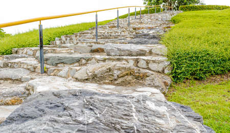 rock stairs made with stone and have yellow bar on it photo