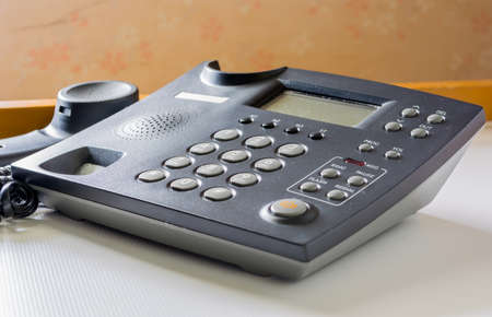 image of telephone with receiver off hook  on table. photo