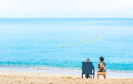 image of  couple sitting on the beach looking on the horizon. photo