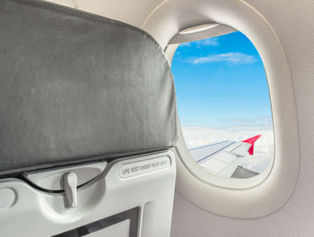 seated: image of  fasten seat belt while seated sign on airplane. Stock Photo