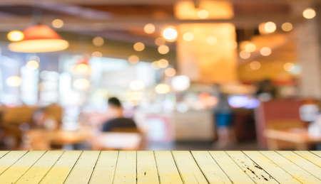Lege houten tafel en wazig koffiebar achtergrond.