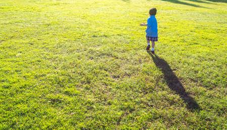 blurr shot of little boy running in the grass field . photo