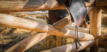 saddle: Leather horse saddle displayed on wooden fence Stock Photo
