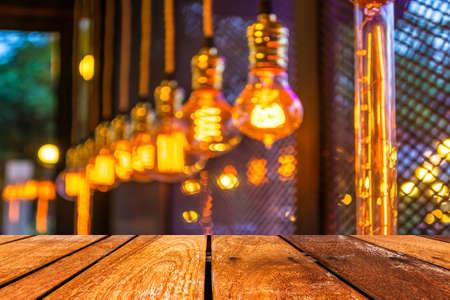 空の木製テーブルとコーヒー ショップは、ピンぼけ画像で背景をぼかし。