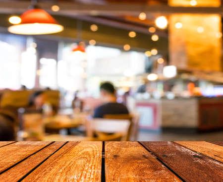 빈 나무 테이블과 나뭇잎 이미지와 커피 숍 배경 흐림.