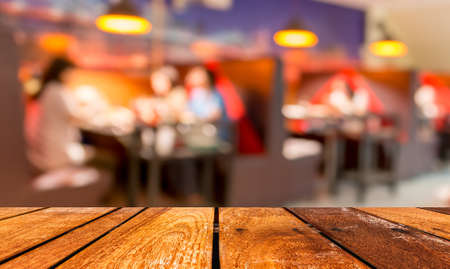 pub: empty brown wooden table and  Coffee shop blur background with bokeh image. Stock Photo