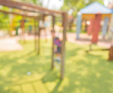niños jugando en el parque: Imagen desenfocada y borrosa de un parque infantil en el parque público para el uso del fondo.