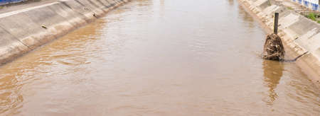 outflow: image of brown water with cement  canal in rainy season.