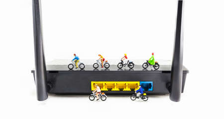 mini bike: image of mini figure dolls riding bike on wifi router  isolated on white background . Stock Photo