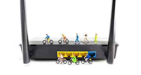 mini bike: image of mini figure dolls riding bike and running on wifi router  isolated on white background . Stock Photo