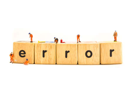 idea concept image of mini figure dolls engineer fixing on wooden toy letter Error isolated on white background. Stock Photo