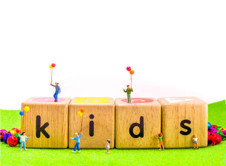 figur: image of mini figure kids dolls hold balloon playing on toys wooden  blocks isolated on white background.