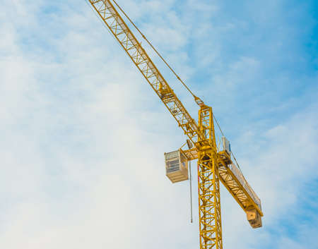 image of yellow crane and blue sky in background. photo