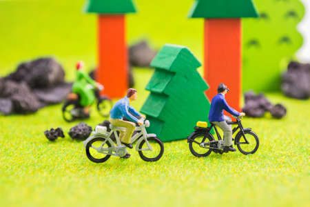 mini bike: image group of people(mini figure dolls) with retro bicycle in a park. Stock Photo
