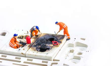 image of mini figure dolls engineer fix Burned plug socket isolated on white background. photo