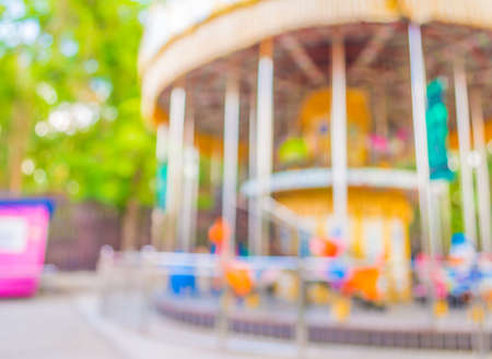 play the old park: blur image of roundabout in theme park for background usage. Stock Photo