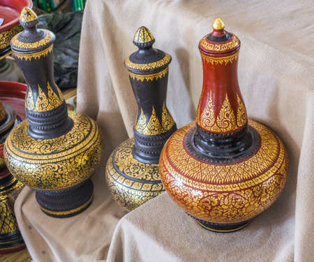made of water: image of Thailand water pot made with clay and decorated with golden oil paint.