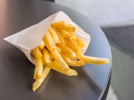 image of french fried on brown wooden table . Stock Photo