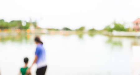 relieved: blur image of people on lakeside with bokeh for background usage.