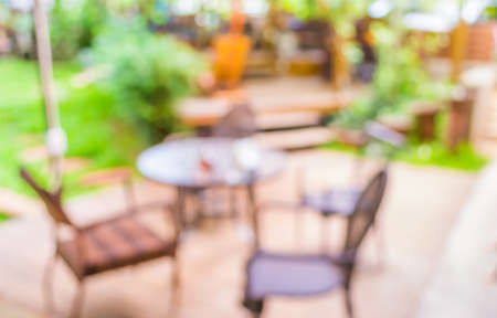 out door: blur image of out door restaurant with green garden in background . Stock Photo