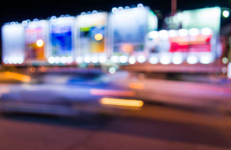 vibrant background: image of blur street  and billboard  with warm colorful lights in night time for background usage .