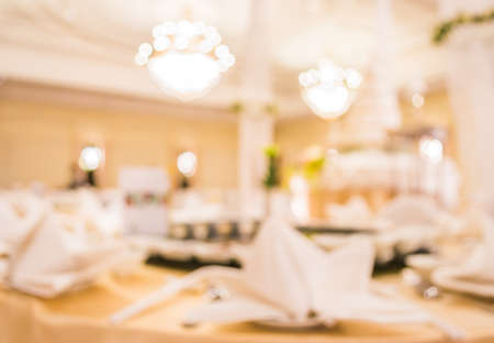 dinner hall: blurred image of Large dining table set for wedding, dinner or festival event with beautiful lights decoration inside large hall with people. Stock Photo