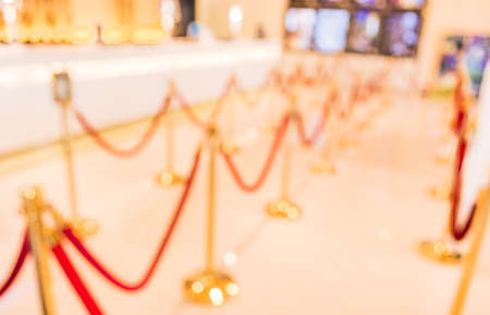 stanchion: blur image of Golden fence, stanchion with red barrier rope in large mall.
