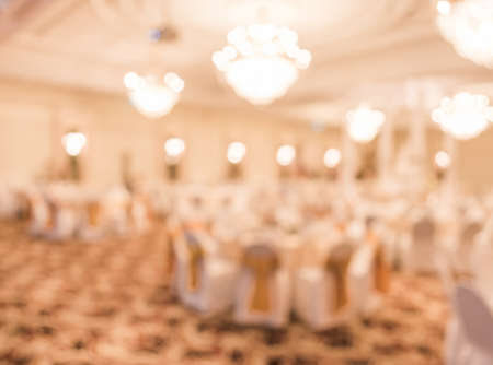 blurred image of Large dining table set for wedding, dinner or festival event with beautiful lights decoration inside large hall with people. Stock Photo