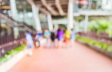blur image of people walking at corridor with open space to the green garden for background usage.
