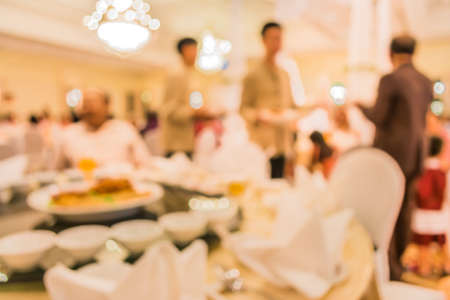dinning table: image of blur people on dinning table set for background usage . Stock Photo