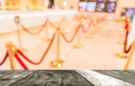 blur image of Golden fence, stanchion with red barrier rope in large mall.