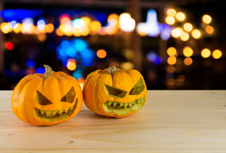 image of orange halloween pumpkin on wooden table  with bokeh in background.