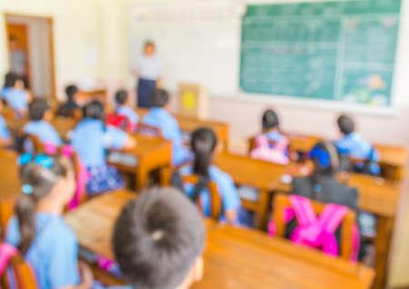 aula: difuminar los niños y profesor en el aula para el uso del fondo. Foto de archivo