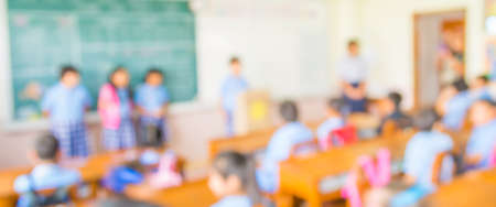 students in classroom: blur kids and teacher in the classroom for background usage. Stock Photo