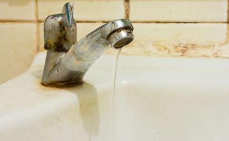 Afbeelding van oude wastafel met beschadigde waterkraan.