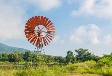 wind force wheel: red wind turbine generator with green mountain and blue sky background.