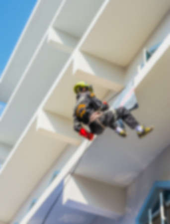 rappelling: blur image of  Firefighter practice rappelling on tall building. Stock Photo