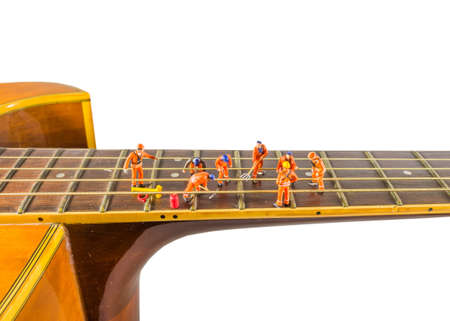 thee: concept idea image of sound engineer doll fixing the guitar string means make thee good music as teamwork. Stock Photo