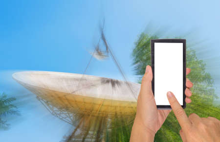 sattelite: male hand is holding a modern touch screen phone and image of large sattelite dish  and blue sky in background. Stock Photo