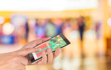 personas caminando: mano masculina es la celebraci�n de un tel�fono de pantalla t�ctil moderna y la imagen borrosa de personas caminando en el centro comercial, el desenfoque de fondo con bokeh Foto de archivo