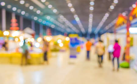 blurred image of people at trade show for background usage .