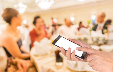 男性の手はモダンなタッチ スクリーンの携帯電話を保持している、バック グラウンドの使用のための大きいホールで結婚披露宴のイメージをぼかし
