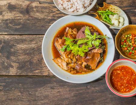 moo: Thai Style pork leg pot stewed(Kao Kha Moo) with rice in white dish on wood table