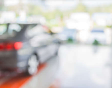 バック グラウンドの使用車ショップのショールームで市販車スタンドのイメージをぼかし。